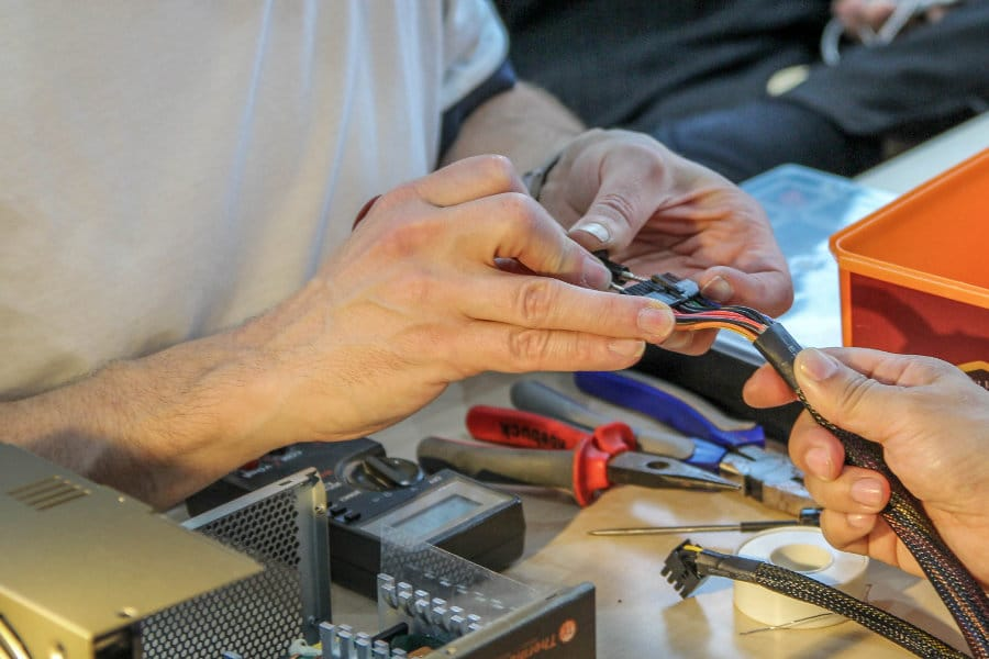 Volunteers at a Restart Party fixing devices, cropped on hands