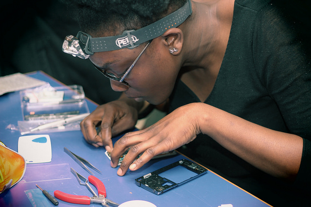 A woman repairing her smartphone at a Restart Party