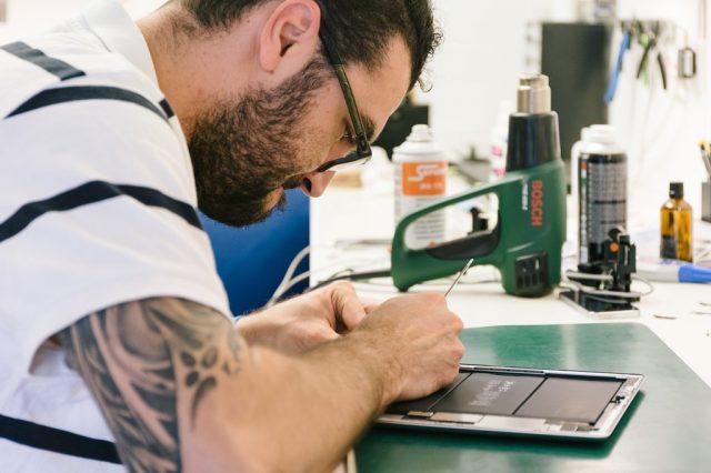 Man repairing an electronic tablet