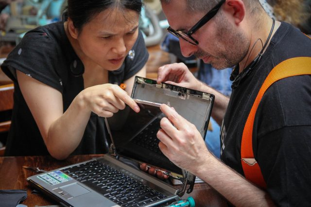 Two people repairing a laptop display